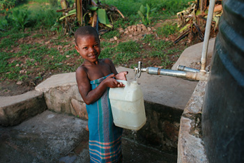 A Rwandan girl collects improved water from a source with ongoing financing in place to ensure sustainability. Credit: Global Water Challenge