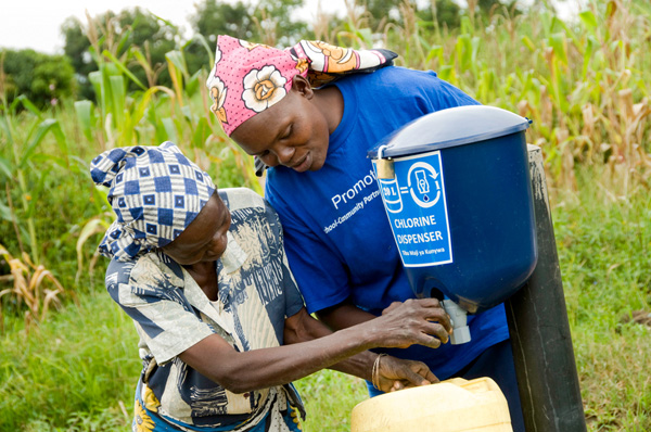 Caroline, the dispenser promoter in Laban Springs, shows a community member how to use the chlorine dispenser. Credit: Jonathan Kalan