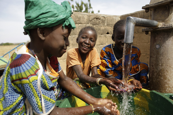 Girls enjoy the clean water from the new water points in Tianfala, Mali. Credit: WaterAid / Layton Thompson