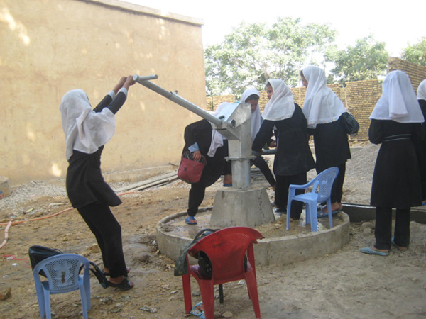 Girls enjoying a reliable source of clean well water at their school.