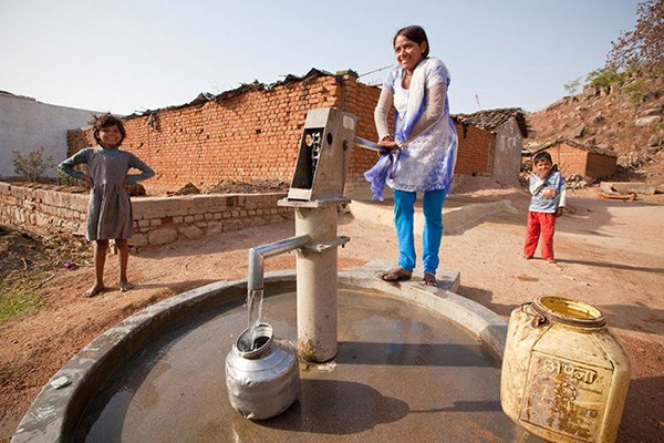 Woman in India pumping water from water point. Credit: charity: water