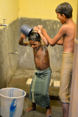 Using piped water in the shower for bathing -- a step towards better hygiene. Credit: Gram Vikas