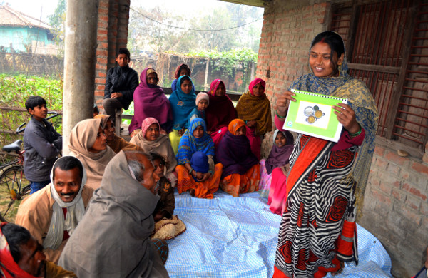 A community business facilitator trained by iDE Nepal generates demand for a hygienic latrine through a group sales meeting focused on the challenges of open defecation. Credit: iDE
