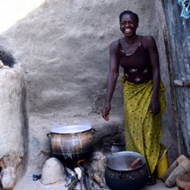 A woman displays her local beer brewing process in rural Burkina Faso. Increased access to water means that women are able to expand their income generating activities. Credit: Winrock International