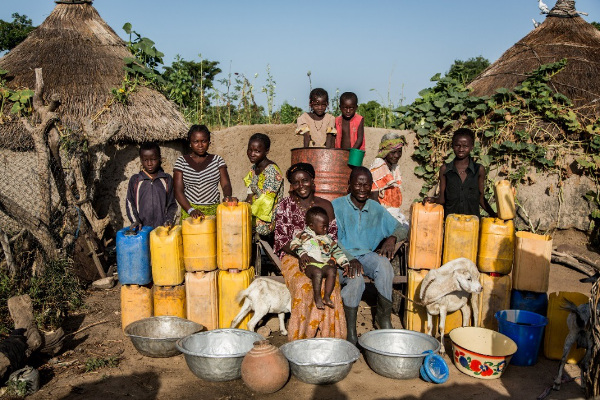 A family with their day's water consumption - 105 gallons for everything from drinking and washing, to cooking, feeding livestock and watering crops. Credit: WaterAid / Andrew McConnell - Nabitenga, Burkina Faso