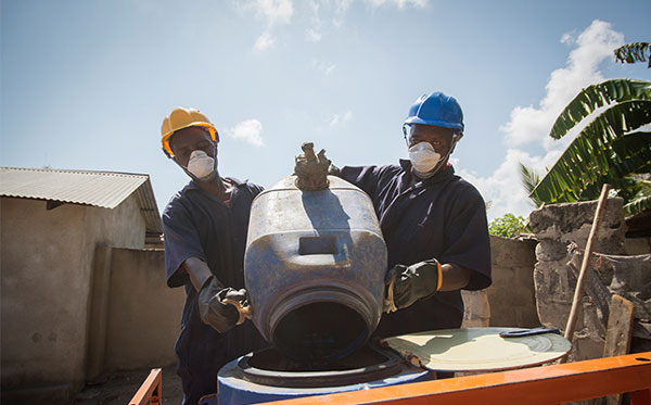 Julius Chisengo and Cleophas Shinga empty the contents of a pit latrine using a Gulper pit-emptying pump, Dar es Salaam City, Tanzania. Credit: WaterAid / Eliza Deacon