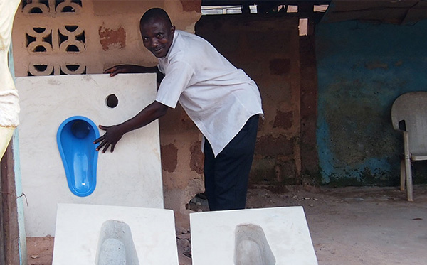 Local business owner, Emeka, with a prototype of the new toilet. Enugu, Nigeria. Photo Credit: WaterAid/Nneka Akwunwa