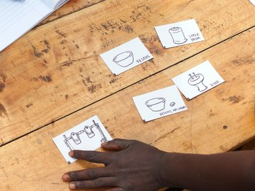 A member of a focus group in Kisumu, Kenya, provides user preference input for a handwashing station customized for areas without access to piped water. Photo Credit: Noel Wilson