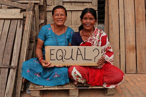 "Two women in Nepal sitting next to each other holding a sign that reads ""equal?"""