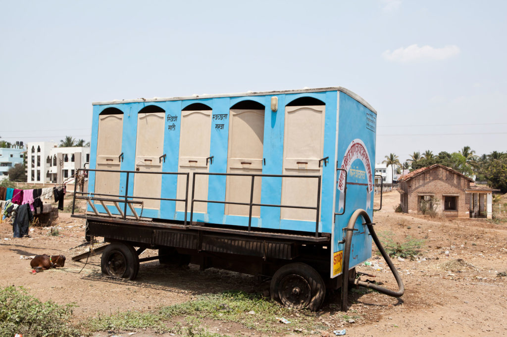 Photo of blue van with five latrines.